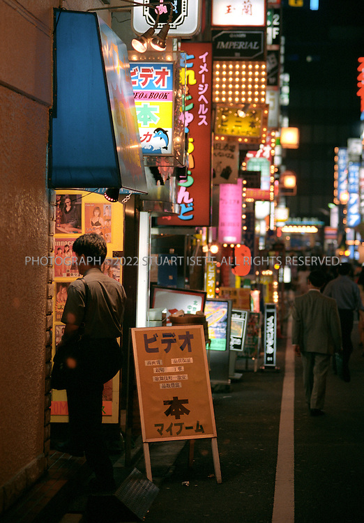 7/1/2001--Tokyo, Japan..A Japanese salaryman slips into a massage parlor in Tokyo's infamous red light district, Kabukicho....All photographs ©2003 Stuart Isett.All rights reserved.This image may not be reproduced without expressed written permission from Stuart Isett.