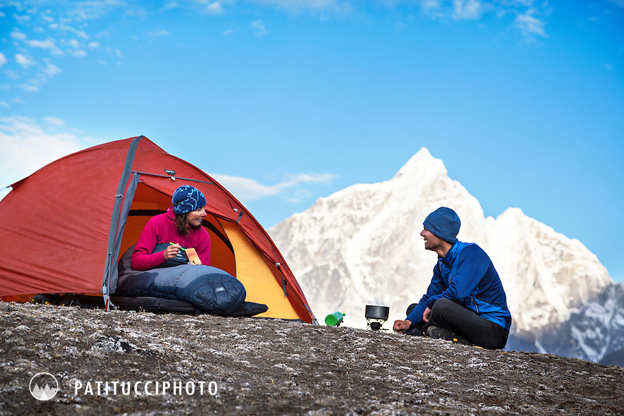 A couple at their tent in the morning using a camp stove, Nepal Himalaya.