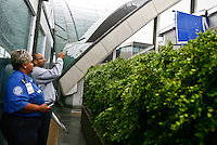 James Allen, of St. Louis, takes a cell phone photo of a sign sticking out of the wall at Lambert- St. Louis International Airport on April 23, 2011 after storms last night damaged both the interior and exterior of the airport. The airport was closed all day today and officials hope to reopen tomorrow. REUTERS/Sarah Conard (UNITED STATES)
