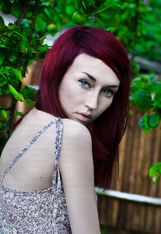 Young red-haired, blue-eyed and pale skinned girl looking over her shoulder at the camera with apple tree and fence background.