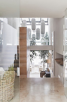 This contemporary house is an exercise in purity and harmony, where restraint and bleached colour allow simplicity and custom-made comfort to come to the fore as a luxury. From the front door you can see all the way through to the living room and veranda. The long white lanterns hanging in the double-volume entrance were specially commissioned and are handmade out of paper.