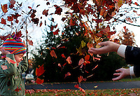 Thursday, November 15, 2007--Ellie Kingston, 3, left, of Webster Groves, laughs as she is showered with leaves by her nanny Rachel Buffa, right, after the two finished raking the leaves in the front yard. .Sarah Conard | Post-Dispatch