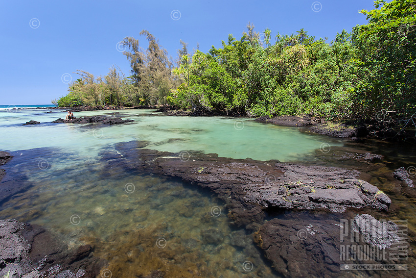 A beach-goer relaxes among the tide pools at Richardson Beach Park, Hilo, Big Island, Hawaii