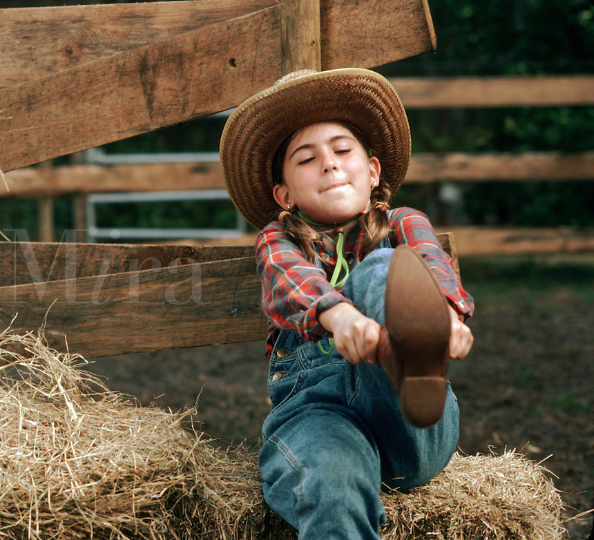 A young girl in a hat sits on a bale of hay in a paddock and pulls on a riding boot with concentrated expression.