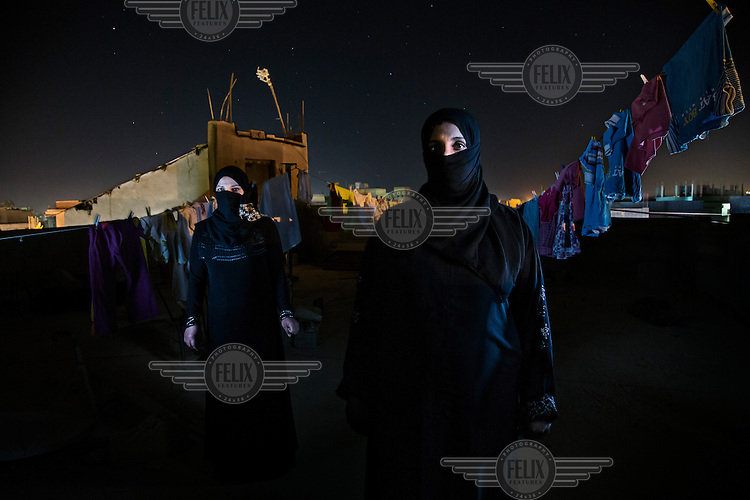 """Syrian refugees, Ihsan, 28, and her cousin, Sammia (left), pictured on a rooftop in Al Mafraq, Jordan. They had crossed the border into northern Jordan 3 days earlier after fleeing the increasing violence in Syria...Words of Ihsan: """"We left our house 3 months ago because there was a lot of shooting and bombing in our area. We went to the grasslands around Homs and moved from place to place. We had a tent and moved 6 or 7 times, drinking water from the springs and receiving food from the local people. My family contains 8 people and  we traveled with 4 other families, we were always afraid of the army finding us. ..After 15 days I returned to my house to get clothes for the children and found everything there destroyed. There were soldiers everywhere in the streets around my house. Two huge men stopped me and pointed their guns at me and questioned me about my husband; I said he was dead. When I got to my house it was destroyed, one side was missing and everything was stolen. The men had followed me and when I left I was shot at, a bullet went past my ear and I ran. I saw many dead bodies on the street, men, women, and children. ..We decided to move to Jordan because the situation was becoming very bad in the country. We moved south from place to place sometimes walking and sometimes by bus. We slept in the open or if it was cold we pitched our tent, when we got to Deraa the Free Syrian Army helped us to cross the border. There was a crowd of around 90 people and we walked together across the countryside and sometimes when the Syrian Army spotlight was shining we had to duck. We gave the children medicine so they would sleep and not make noise. I am 7 months pregnant but I wasn't worried about my baby because I am used to being in this situation. I have been in Jordan for 3 days and I feel safe and calm, there are no sounds of bullets or bombs"""". ..."""