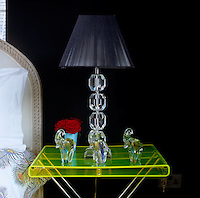 Close-up of an acid green Perspex bedside table in the otherwise black and white bedroom
