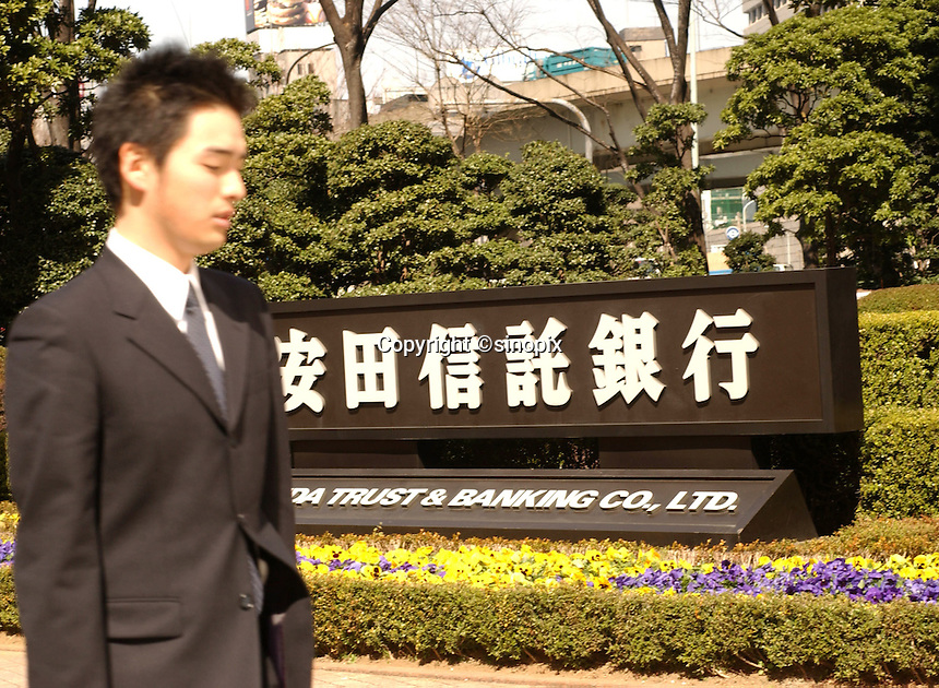 Businessman passes Yasuda Trust Bank in Tokyo banking and business district called Otemachi..