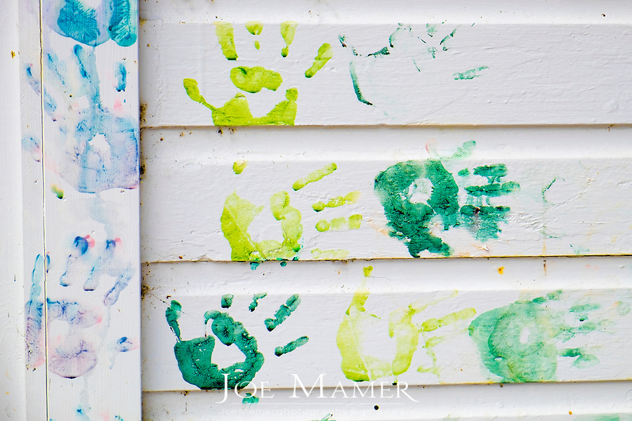 Colorful paint hand prints on a white clapboard wall.
