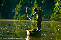 Yine or Piro Indian on his dugout canoe, fishing with bow and arrow in an oxbow lake in lowland tropical rainforest, Manu National Park, Madre de Dios, Peru.