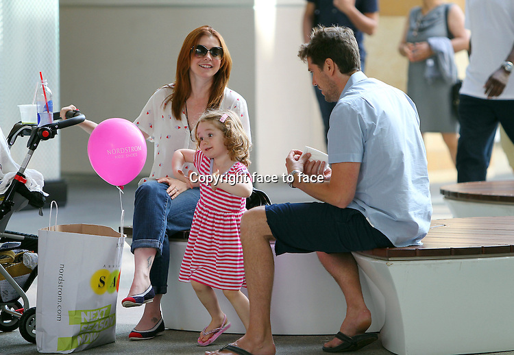 """Is that a Robot-Dance? Alyson Hannigan and hubby Alexis Denisof crack up while little Satyana horses around during a shopping break at the Santa Monica mall. Baby Keeva_was sleeping in the stroller while Alyson and Alexis talked about the newly purchased cute baby romper with the """"i'm going back to CALI"""" print. Notice Alyson's trendy cupcake-print blouse! Los Angeles, California on 3.8.2012..Credit: Correa/face to face.."""