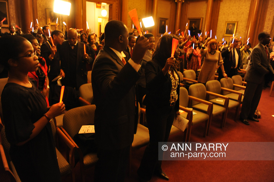 January 11, 2012 - Brooklyn, New York, USA: Commemorating the 2nd anniversary of the Mw 7.0 earthquake in Haiti, people hold up glo-sticks at 2nd Annual Interfaith Memorial Service for Haiti, Wednesday night at Brooklyn Borough Hall.
