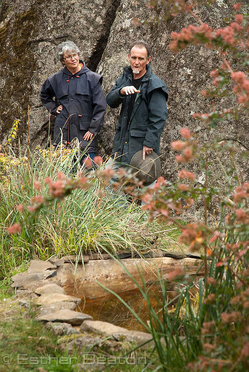 Marcia McCartney and Wayne Stokes, granite boulder with pond, on their hobby farm and covenanted land 'Marway', near Tumbarumba, New South Wales