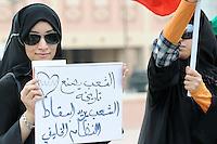 """BAH309 MANAMA (BARÉIN) 25/2/2011.- Una mujer muestra un cartel en el que se puede leer """"la población está marcando su victoria"""" durante una durante una marcha por las calles de Manama, Baréin, para exigir la dimisión del gobierno de Baréin hoy, viernes, 25 de febrero de 2011. EFE/Mazen Mahdi.."""