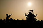 A mikoshi and supporter in silhouette at sunrise during the Hamaorisai matsuri on Southern Beach in Chigasaki, Kanagawa, Japan. Monday July 18th 2005. The festivals marks the celebration of Marine Day in of July. Over thirty Mikoshi or portable shrines are carried through the night from surrounding shrines to arrive on the beach for sunrise. They are then carried into the surf to purify them.