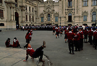 Children play while waiting for the Changing of the Guard at the Government Palace at the Palacio de Gobierno. <br /> The Palacio is located on Plaza Mayor or the Plaza de Armas in downtown Lima. Founded by Francisco Pizarro in 1535, the city is located along the desert coast.  After a disastrous 1746 earthquake, Spanish colonial architecture was built in the period following.