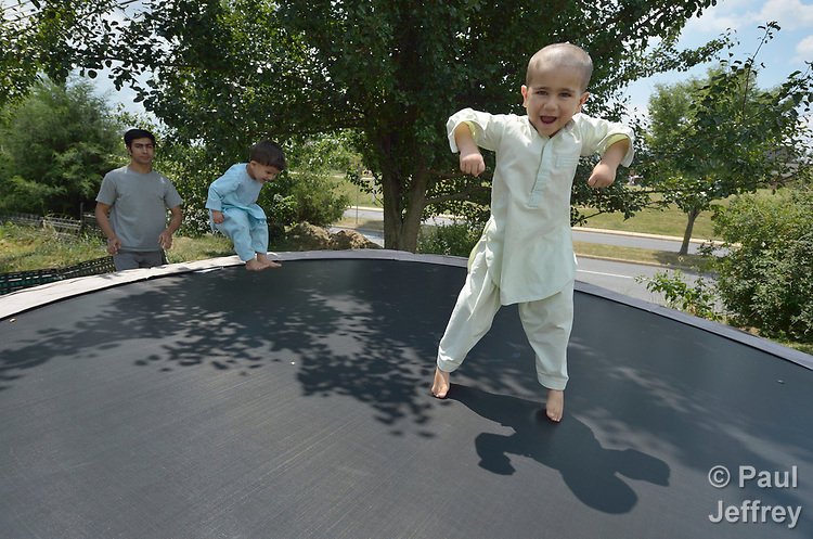 Nasratullah Ahmadzai, 4, bounces on a trampoline with his brother, Sanaullah Ahmadzai, 2, as their father, Ahmadullah Ahmadzai, watches in the yard of their home in Harrisonburg, Virginia. Refugees from Afghanistan, they were resettled in Harrisonburg by Church World Service.<br /> <br /> Photo by Paul Jeffrey for Church World Service.