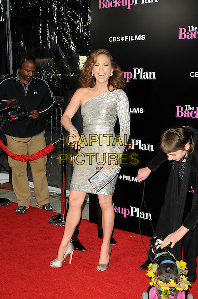 "JENNIFER LOPEZ .arriving at the premiere of CBS Films' ""The Back-up Plan"" at the Regency Village Theatre in Westwood, California, USA, April 21st, 2010..arrivals full length one shoulder silver dress sleeve shiny shimmery clutch bag shoes mouth open smiling dog animal peep toe trolley flowers funny laughing mouth open hand .CAP/ROT.©Lee Roth/Capital Pictures"