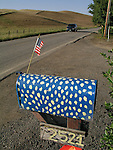 A blue with white dot mailbox is made patriotic with a fluttering US flag along a rural road in San Benito County.