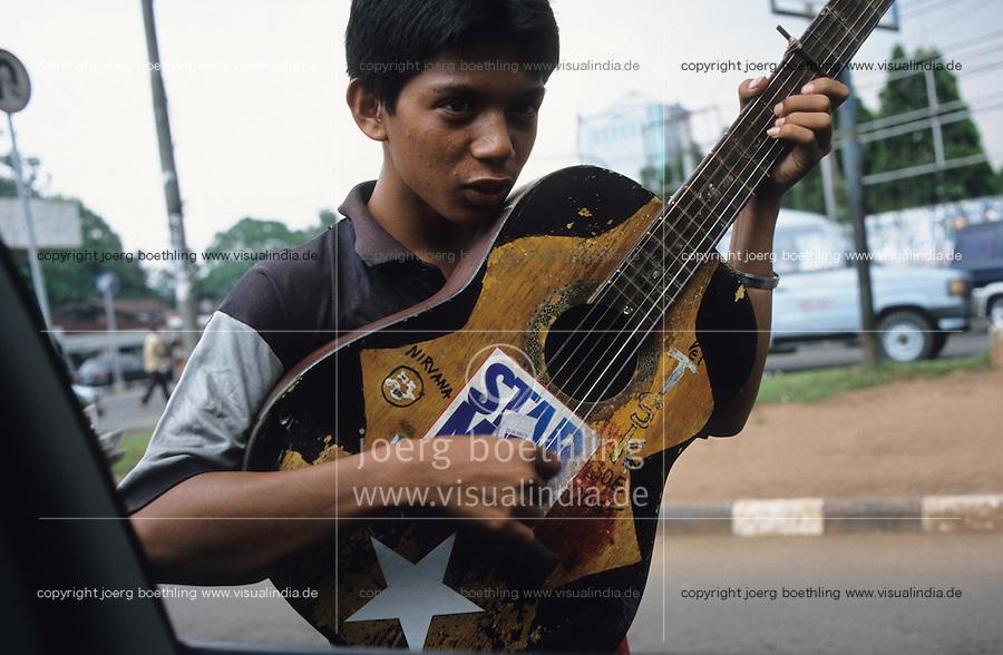 Indonesia, Jakarta, street musician with guitar / Indonesien Jakarta, Jugendliche verdienen Geld mit Gitarre spielen auf Strasse