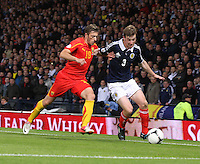Paul Dixon chased by Agim Ibraimi in the Scotland v Macedonia FIFA World Cup Qualifying match at Hampden Park, Glasgow on 11.9.12.
