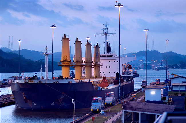 A ship is lowered into the Miraflores Locks on the Panama Canal, one of three locks on the canal that allow ships to transit through the canal.  Locomotives help maneuver the ship through the lock and back into the Canal.