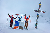 Skiers stand laughing outside the Bella Vista Hut during a whiteout, the sign says to enjoy the beautufl view... during the Öztal ski tour, Austria