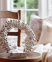 A wreath of silver baubles hangs by a length of ribbon from the back of a chair in the living room