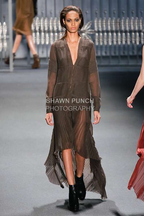 Joan Smalls walks runway in a charcoal chiffon multi-pleated long-sleeve gown with high-low hem and self-covered buttons, from the Vera Wang Fall 2011 collection, during Mercedes-Benz Fashion Week Fall 2011.