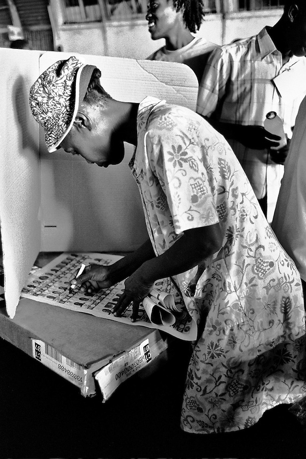 Woman voting behind folded cardboard at the closet voting station to Cite Soleil on the day of the elections in Port-Au-Prince.