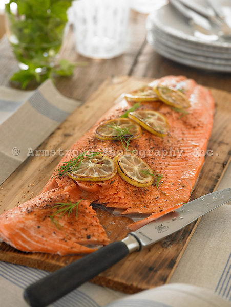 A whole fillet of salmon, cooked on a cedar plank, with slices of lemon, fresh dill, and spices on top