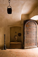 An antique studded door opens into the vaulted entrance hall of the restored palazzo