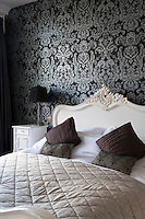 A double bed with a carved headboard in a bedroom decorated in patterned Osborne & Little wallpaper