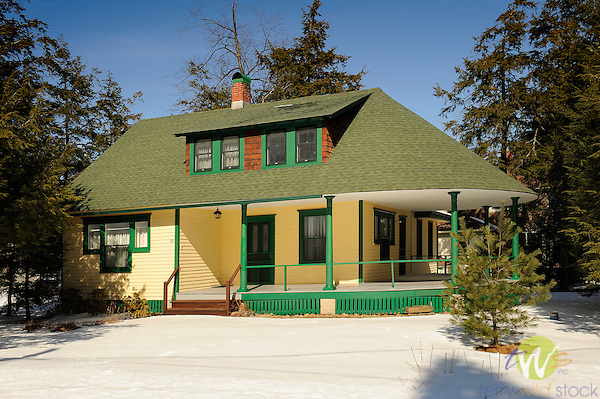 Yellow and Green cottage with rounded porch in winter. Eagles Mere, PA.