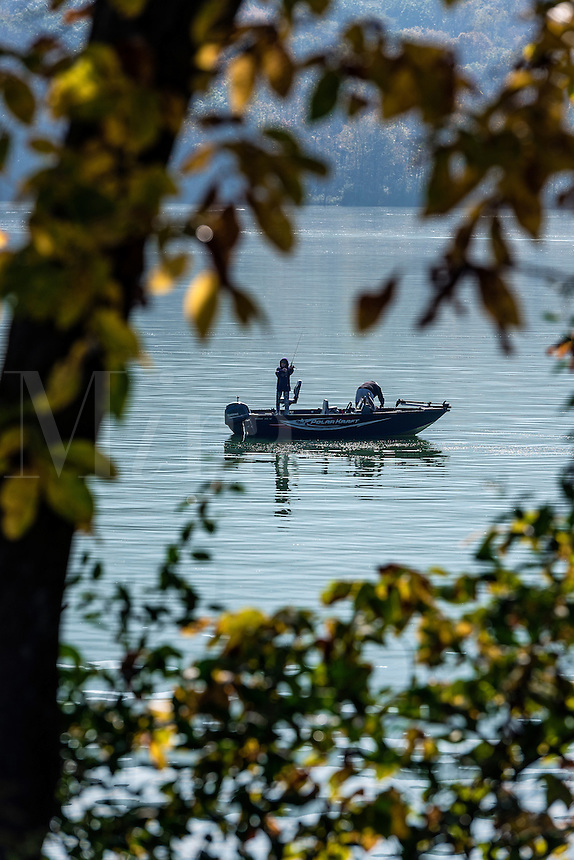 Fishing from a small motorboat on Sayers Lake, Howard Township, Pennsylvania, USA
