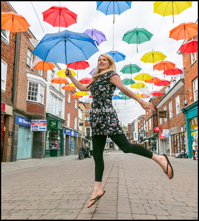 BNPS.co.uk (01202 558833)Pic: LeeMcLean/BNPS<br /> <br /> Marketing & Communications Manager at Salisbury District, Kara Rogers, at the newly erected art installation in the heart of Salisbury.<br /> <br /> A special art installation featuring 90 umbrellas has been erected in Salisbury to attract visitors as the beleaguered city attempts to recover after the devastating poisoning fall out.<br /> <br /> The multicoloured brollies have been hung 15ft above the High Street and will be in place until the autumn.<br /> <br /> They shelter 10 illuminated doves which send a message of 'hope and peace' in the aftermath of the deadly Novichok nerve agent attacks in March.