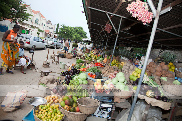 "Women sell fruits and vegetables at the ""Les Cocotier"" market in Cotonou, Benin."