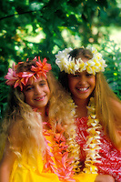 Two beautiful young girls dressed up in leis and muumuus