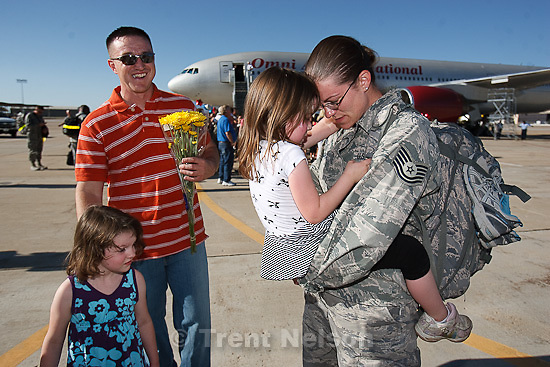 Trent Nelson  |  The Salt Lake Tribune.Tech Sergeant Laura Wright, right, holds her daughter Alexis while her husband Shane and daughter Katie wait their turns as the 729th Air Control Squadron returned to Hill Air Force Base in Layton, Utah, after six months in Afghanistan Wednesday, July 20, 2011.