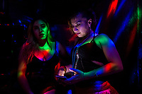A Salvadoran sex worker chats on the phone while talking with her co-worker in a night sex club in San Salvador, El Salvador, 25 November 2018. Although prostitution is not legal in El Salvador, dozens of street sex workers, wearing provocative miniskirts, hang out in the dirty streets close to the capital's historic center. Sex workers of all ages are seen on the streets but a significant part of them are single mothers abandoned by their male partners. Due to the absence of state social programs, they often seek solutions to their economic problems in sex work. The environment of street sex business is strongly competitive and dangerous, closely tied to the criminal networks (street gangs) that demand extortion payments. Therefore, sex workers employ any tool at their disposal to struggle hard, either with their fellow workers, with violent clients or with gang members who operate in the harsh world of street prostitution.