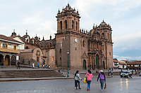 Peru, Cusco.  Young Women Walking in the Plaza de Armas; Cathedral in Background.