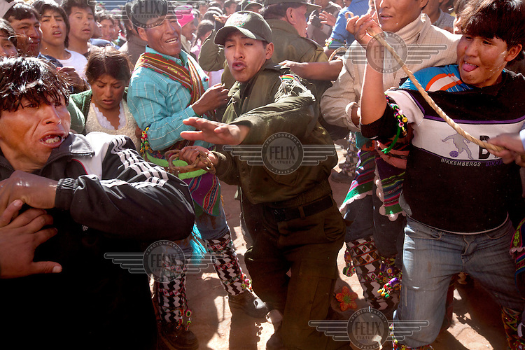 A police man steps in during the ritual fighting in the plaza of Macha. <br /> <br /> The people of Macha and surrounding communities carry on the pre-Columbian tradition of ritual fighting. The communities gather on the plaza of Macha to fight and dance in competition with each other. The blood that is spilled is an offering to Mother Earth. In return, the people ask for rain and a good harvest. This ritual is called tinku or fiesta de la cruz since the cross is also engaged in the festivities. The cross is dressed up, given offerings and brought from communities around Macha to the church in town. This syncretic festival melds pagan, pre-christian rituals with Catholic practice. /Felix Features