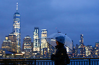 EXCHANGE PLACE, NJ - JANUARY 29: A woman covers herself of the rain as the One World trade Center is seen at the background on January 29, 2019 in Exchange Place, New Jersey. Government officials urged New York to prepare for snow and cold temperatures on the state. the National Weather Service has issued flooding and winter weather warnings and advisories for different areas of the state. (Photo by Eduardo MunozAlvarez/VIEWpress)