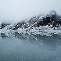 Clouds hide mountain peaks over frozen water of lake Nedreheimredalsvatnet, Eggum, Vestvågøy, Lofoten Islands, Norway