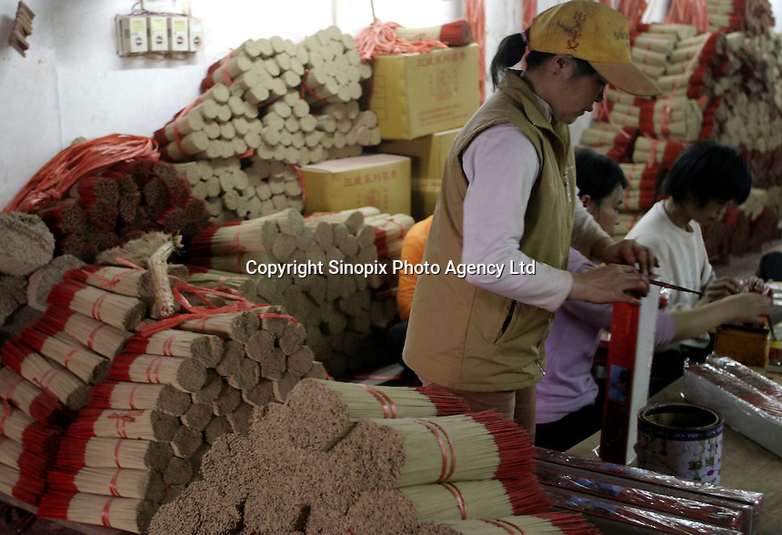 A wroker packages incense at the Meizhengxiang Incense Factory near Xiamen, Fujian Province, China. As religous life increasingly becomes an important part of China, businesses related to religion such as Buddhism and Daoism have flourished. The factories have seen its sales quadruple since its establishment in 1996, reaching euro 5 million in 2003. The factory now employs over 200 workers, mostly migrants from Sichuan and Jiangxi Province..17-MAR-04