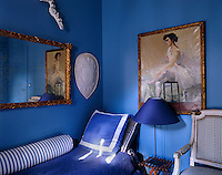 In the guest room a gilt-framed painting and mirror are displayed above the single bed which is covered in deep blue fabric with a striped blue and white bolster