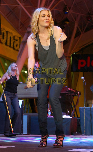LEANN RIMES.Performs during ACM Weekend at the Fremont Street Experience in Downtown Las Vegas, Las Vegas, Nevada, USA, .04 April 2009..country music live on stage gig concert full length jeans gladiator sandals heels black grey grey top microphone hand .CAP/ADM/MJT.©MJT/Admedia/Capital Pictures