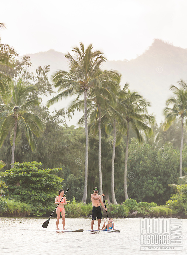 A family learns to standup paddle on Wailua River, Kaua'i.