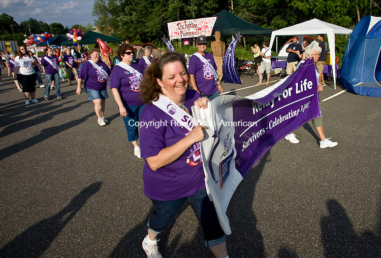 THOMASTON, CT - 25 JUNE 2010 -062510JT05-<br /> Margaret MacDonald Hrebik, left, of Naugatuck, laughs as she leads the victory lap of cancer survivors at the start of Friday's Relay for Life, a fundraiser for the American Cancer Society, at Thomaston High School. MacDonald, a breast cancer survivor, has been cancer-free for six years. The event started at 6 p.m. and continues for 15 hours.<br /> Josalee Thrift Republican-American