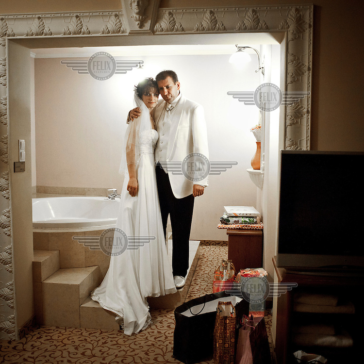 Newlyweds Anna Bogatek and Andrzej Platek in the  bathroom of their suite in the Venecia Palace Hotel. The hotel was built in 2008 by Polish businessman Waclaw Gozlinski, who concluded that potential guests, exposed to a diet of American B movies and television soap operas, have developed a taste for kitch for their parties and weddings. As Poles are getting richer, the hotel is now the most popular wedding party venue in Poland and needs to be booked over a year in advance.