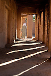Traditional dressed man walks through a arch way at a kasbah in Ouled Driss, Morocco.